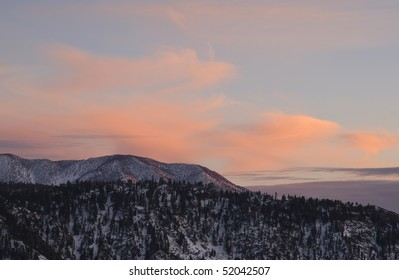 sun setting in the san bernardino mountains on the way down from big bear lake,with colorful clouds surrounding the snowy mountain peaks,california,december 2009.