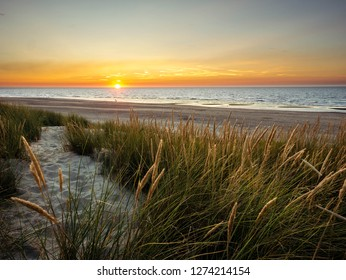 Sun setting in the sea in front off colorful marram grass covered dunes in northern France