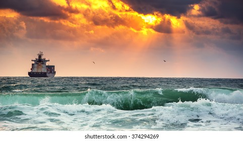 Sun setting at the sea with sailing cargo ship, scenic view