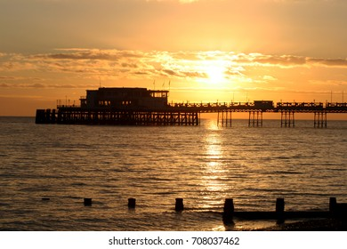 Sun setting at Worthing Pier West Sussex England UK
