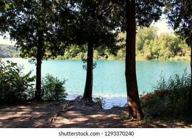 Sun and shade with dirt path that leads through trees and view of beautiful blue-green waters of lake, where frigid waters of melting glaciers did not mix with warmer waters below.