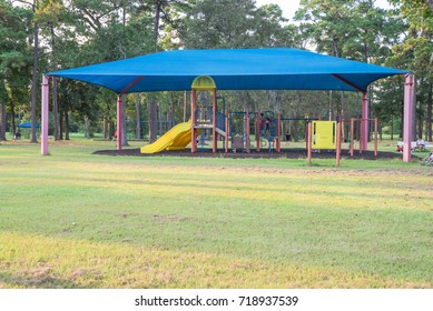 Sun shade playground at grassy public park in Houston, Texas, US. Safe, comfort covered playground for kids play all day. Sail fabric canopy blocks up to 90% harmful UV rays. Unidentified kids playing