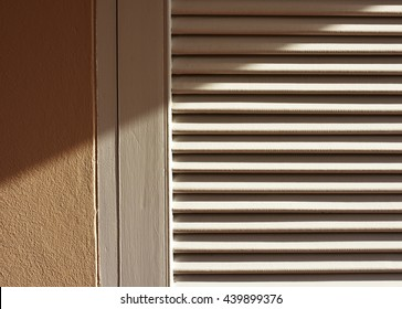 Sun shaded wooden door frame and panel painted white with light brown cement wall. Late afternoon sunlight provides lines and shade. Wooden blinds door in sunlight.