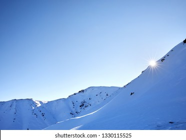 Sun in shape of star is rising at mountains with snow and glacier at winter time