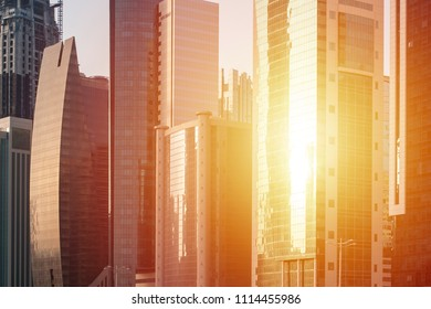 Sun shine in glass of skyscrapers windows. City landscape background
