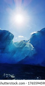 The sun shines above a glistening glacial blue iceberg in Antarctic waters