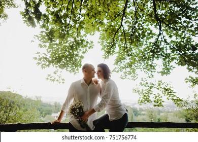 Sun shines around stunning couple hugging under green trees