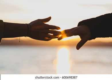Sun shines behind hands of man and woman reaching fingers to each other
