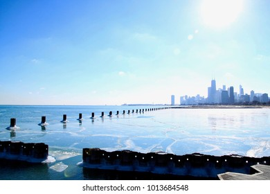 Sun shines bright over Chicago skyline which is reflected on a frozen Lake Michigan