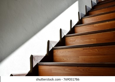 The sun shines down on the wooden stairs in the building.