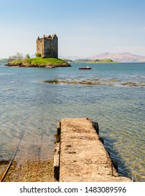 Sun shines on the defensive island house of Castle Stalker in Loch Linnhe in Argyll in the West Highlands of Scotland, as featured in Monty Python and the Holy Grail.