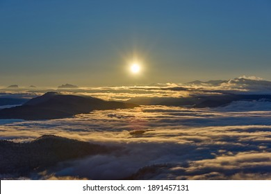The sun shines on a misty mountain valley