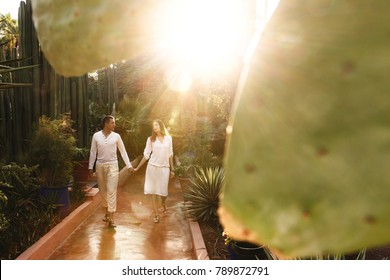 Sun shines over couple in white closes walking around