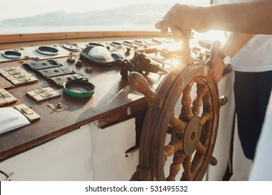 Sun shines over the wooden wheel held by man
