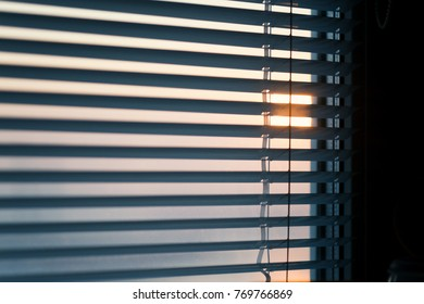 The sun shines through the blinds. Selective focus.