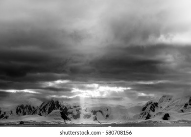The sun shines through the clouds in black and white, antarctic peninsula.