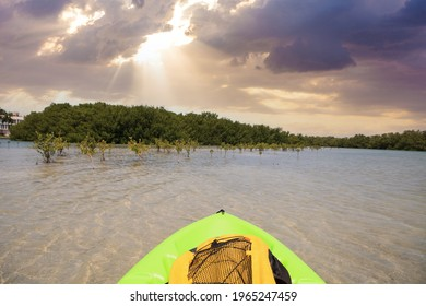 Sun shines through the clouds over a Green Kayak in the water of New Pass in Bonita Springs, Florida