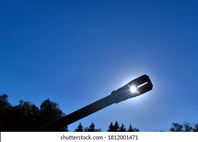 sun shines through the cracks in artillery gun against blue sky and blurred treetops
