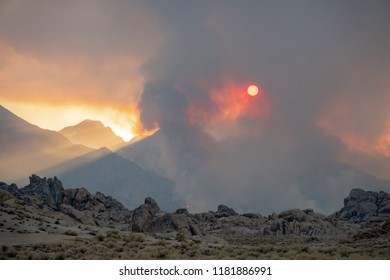 Sun shines through the smoke of the Georges Fire, a California Wildfire in the Eastern Sierra Nevada Mountains in 2018, over the rocky Alabama Hills recreation area