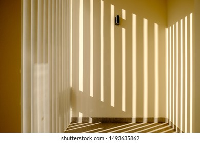The sun shines through a steel lattice screening an entrance in a Middle Eastern, high-end, luxury housing development on a sunny day with strong shadows.