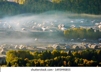 The sun shines in the yellow forest woods and the morning fog of the village, which is the autumn scenery of the colorful Chinese Hemu Village log cabin.