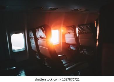 Sun Shining From Airplane Aircraft Plane Window In Cabin Cabin. Bright Sun Rays At Sunset Sunrise.