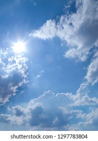 Sun shining in blue sky with clouds on summer day
