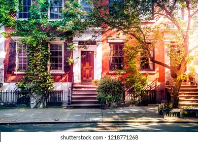 Sun shining down on a beautiful street with brownstones in West Village, New York