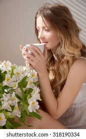sun is shining into the bedroom, she looks out the window. Hand and cup. lady sitting beside the bed, her hand near her head, she looks into the camera. Morning coffee, enjoyment