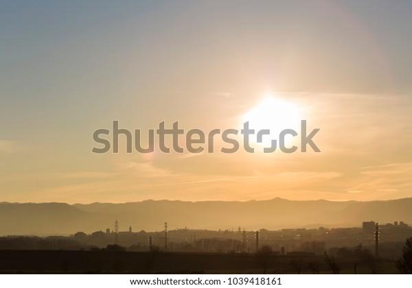 Sun shining on a foggy dawn orange landscape