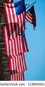 The sun shining on multiple American flags hanging from a building in New York.