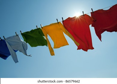 Sun shining over a laundry line with bright clothes on a windy day.