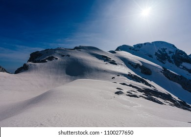 Sun shining over a snow covered alpine landscape. Blue sky and high alpine peaks and summits of Kamnik Savinja Alps, Slovenia. Turska Gora. Great sunny day, sunstar and snow mountain adventure.