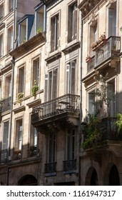 sun shining slantways across the faded grandeur of a row of buildings with balconies in Bordeaux old town.