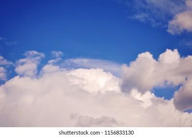 The sun shining through a cloud in a blue sky.
