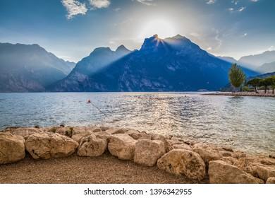 the sun is shining through clouds behind mountains, Torbole beach, Garda lake, Italy