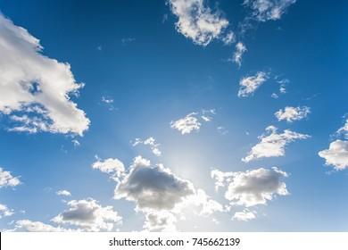 Sun shining through clouds on a clear blue sky