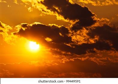 sun shining through clouds at sunset
