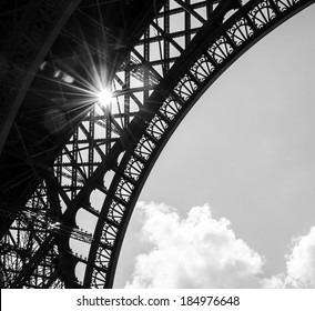 Sun shining through Eiffel Tower. Sun beams and spots. Aged photo. Black and white.
