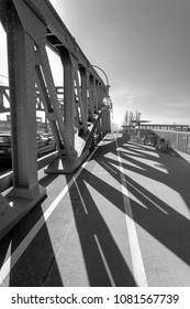 Sun shining through the pillars of a bridge, casting long shadows - Infrared black and white