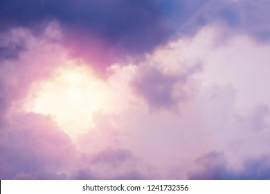 Sun shining through pink and violet dramatic clouds in sky. For background and wallpaper with copy space