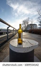 Sun shining through a Wine Bottle, standing on a Bollard, on a Dock, on mild Winter Morning