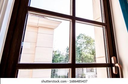 The sun is shining through the wooden door frame windows