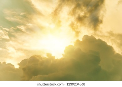 Sun shining through yellow dramatic clouds in sky. For background and wallpaper