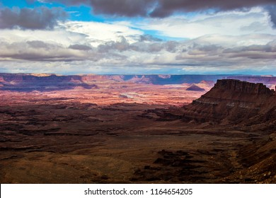 The sun is shining upon the background land formations in this panoramic view of the Needles Overlook in Canyon Rims Recr. Area near Monticello, Utah. The steep foreground cliffs are in full shadow.