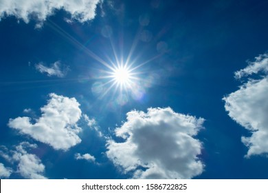 Sun Shining With White Clouds Against Blue Summer Sky