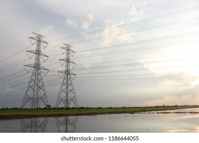 The sun is shining.Hight power transmission tower are located on a green field.Many wires are tied a cross The water to see the full field.