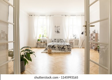 Sun shinning through windows into a spacious stylish bedroom interior in a villa. Big bed with bedding standing on herringbone parquet. Real photo. Empty floor.