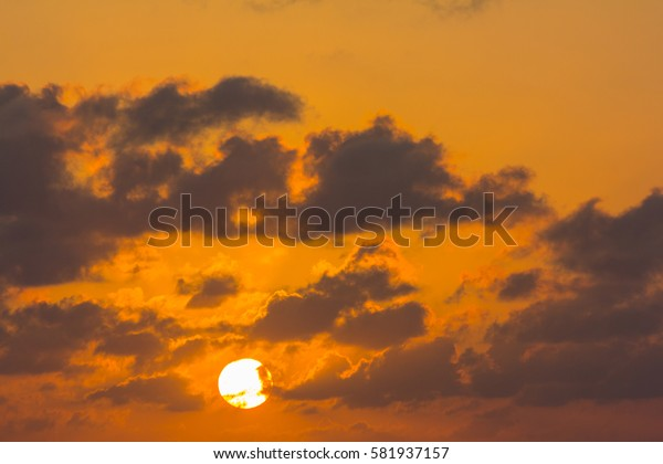 sun in the sky at sunrise in yellow-gold clouds