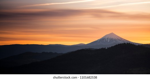 The sun slips down below the horizon and leaves rich saturated orange color around Mt. McLoughlin in the Cascade Range